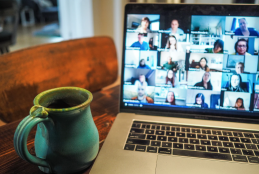 A cup next to a laptop showing participants on a video call